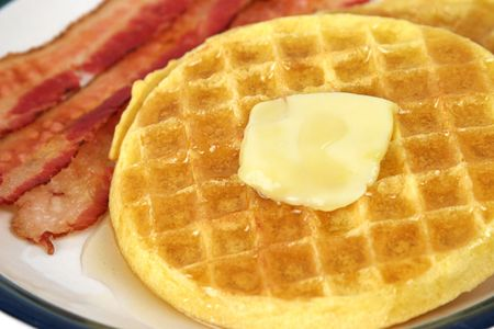 A closeup shot of waffles dripping with butter and syrup with bacon on the side. Imagens