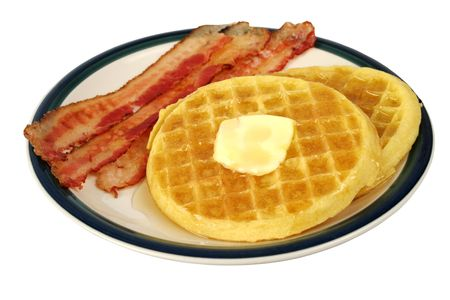 carbs: A plate of waffles with butter and syrup with bacon on the side.  Complete plate, isolated.