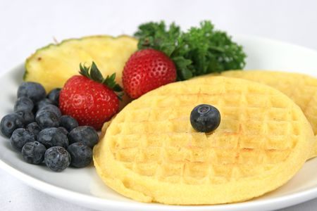 A side view of a plate of waffles with fruit.
