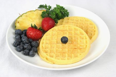 carbs: Waffles served on a white plate with a side of fruit.  Complete plate visible on white background.
