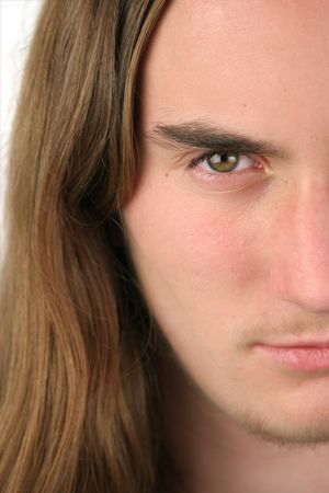 boy long hair: A half portrait of a serious looking teenaged boy with long hair.