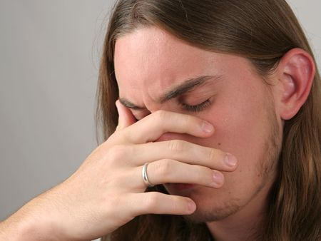 pressured: a teenaged boy with his head in his hands, very depressed or with a headache Stock Photo