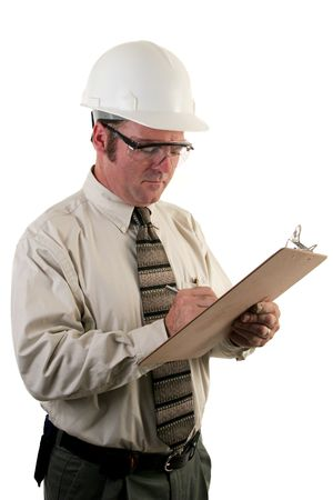 inspector: a construction safety inspector with safety goggles and a hard hat inspecting a jobsite Stock Photo