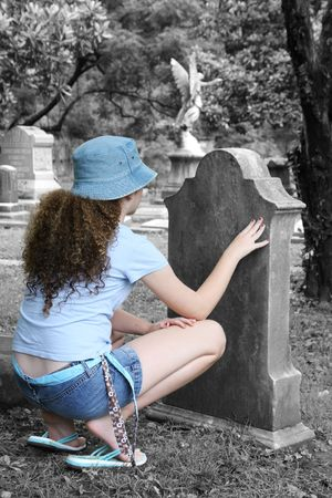 a young girl lookin at a tombstone in a graveyard