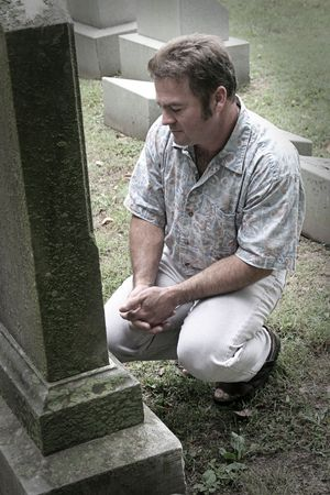 a man in a graveyard with hands folded in reverence - partly desaturated 免版税图像