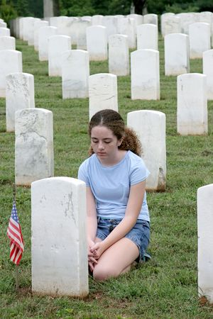 teenaged: a young girl mourning a fallen soldier in a graveyard Stock Photo