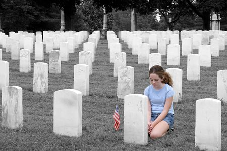 honoring: a young girl in a military cemetary honoring a fallen soldier  - selective colorization Stock Photo