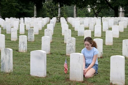 honoring: a young girl in a military cemetary honoring a fallen soldier