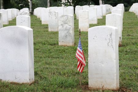 sacrificed: a soldiers grave with an american flag, in a military graveyard