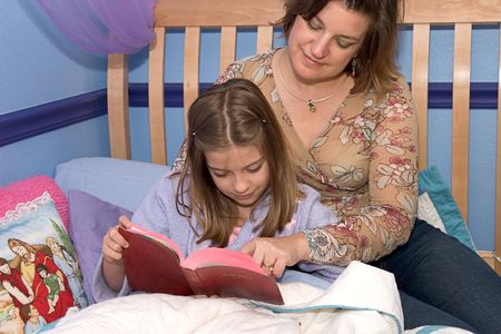 A mother and daughter reading bible stories at bedtime photo