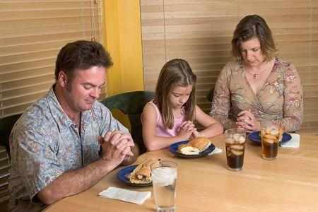 familia orando: Una familia que dice tolerancia sobre su comida de la hora de comer