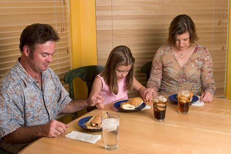 family praying: A family saying grace over their lunchtime meal