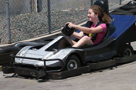 teenaged girls: A young having fun racing a go cart around a track Stock Photo