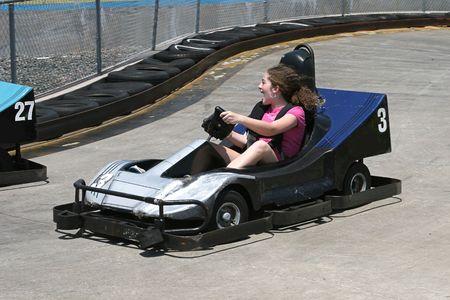 racecourse: a girl racing a go cart around a racecourse
