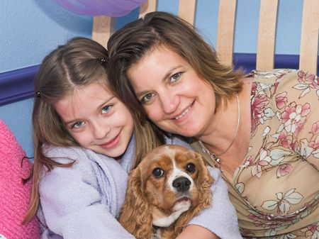 cavalier: a mother and daughter posing with their cavalier spaniel dog