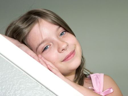 A little girl resting her head on her hands looking sleepy - diagonal Imagens
