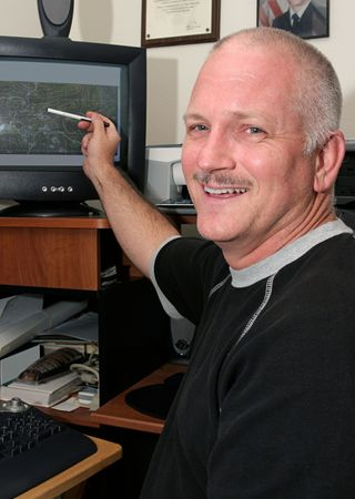 A meteorologist (weather man) pointing to his computer and smiling.  He has good news about the weather. Stock Photo - 1406826