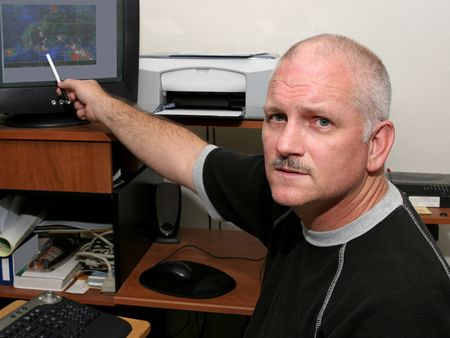 A meteorologist pointing out a hurricane developing.  He has a serious expression. Stock Photo - 1406827