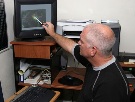 A meteorologist tracking a hurricane on his computer and pointing out the eye. (focal point is his headface)