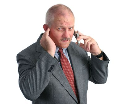 a man trying to hear his cellphone in a loud place - he looks annoyed Stock Photo - 230224