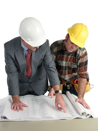 An engineer and a construction foreman reviewing blueprints - isolated photo