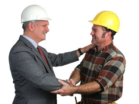 warmly: an engineer and a construction foreman greeting eachother warmly on the job