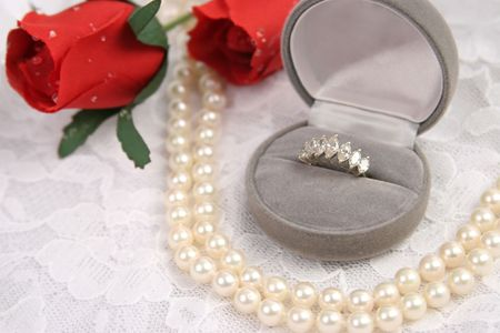 a diamond ring, string of pearls and roses on a lace background photo