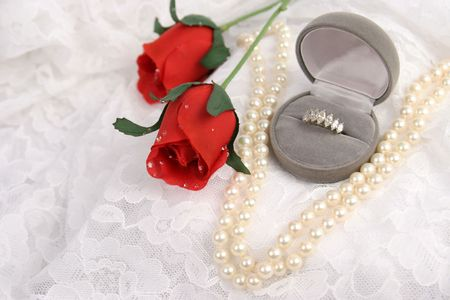 a diamond ring, string of pearls, and silk roses on lace - room for text photo