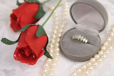 andamp: an engagement ring, pearls andamp,amp, red roses on lace Stock Photo