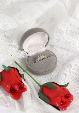 a wedding ring and silk roses on lace. Room for text.