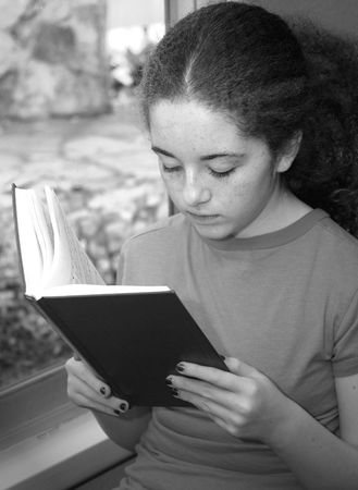 hymnal: A young girl in church reading a hymnal by window light - Black & White Stock Photo