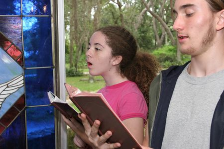 hymnal: a teen boy and girl  singing hymns in church (focus is on girl)