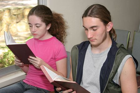 hymnal: a teen boy and girl in church opening their hymnals (focus is on boy) Stock Photo
