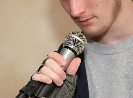 ballad: a closeup of a microphone with a man speaking into it (focus is on hand and microphone) Stock Photo