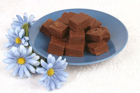 sinful: homemade fudge on a blue plate with blue flowers on a lace tablecloth.