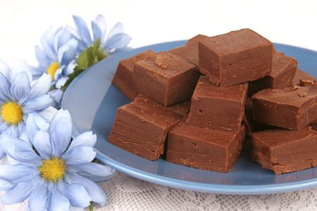 chocolaty: homemade fudge on a blue plate with blue silk flowers for decoration. Stock Photo