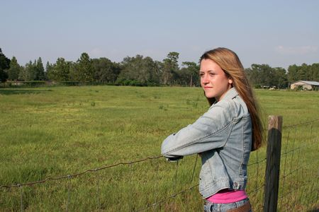 a beautiful girl on a ranch, leaning on a fence looking at a field, with a barn in the distance photo