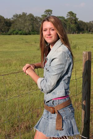 jeans skirt: a beautiful girl leaning on a fence in the country