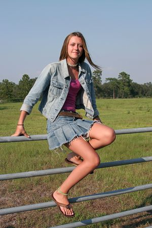 a beautiful farm girl sitting on a fence with a meadow behind her