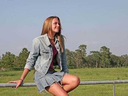 denim: Una hermosa ni�a sentada sobre una valla en el pa�s, mirando hacia el cielo.