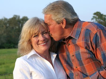 an attractive man giving his beautiful wife a kiss on the cheek photo