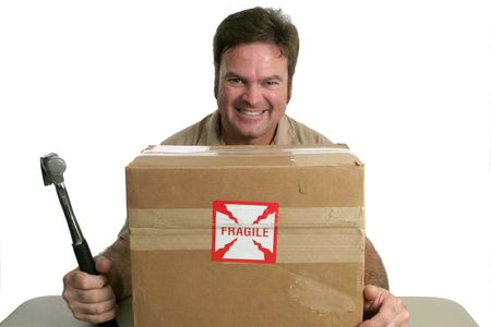 A delivery man with a package marked fragile.  He is about to hit it with a hammer. Stock Photo - 245200