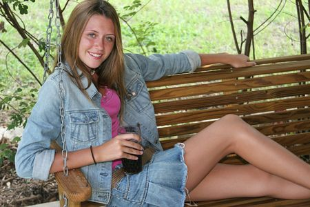 teenaged girls: A beautiful teen girl enjoying a cold drink on a porch swing