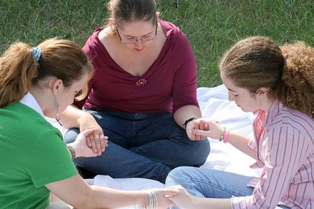 jesus adolescent: A group of teen girls having a prayer circle outdoors. Stock Photo