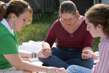 christian faith: Three teen girls gathered outdoors to pray.