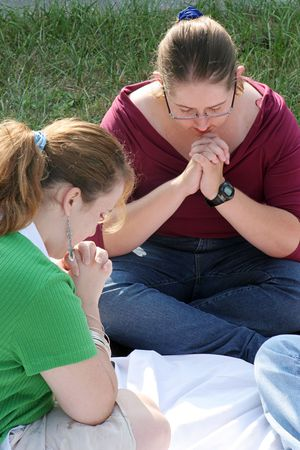 jesus adolescent: A closeup of two teen girls in prayer. Stock Photo