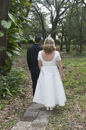 wooded path: A newlywed couple headed down a wooded path, as a metaphor for the pathway of life. Stock Photo
