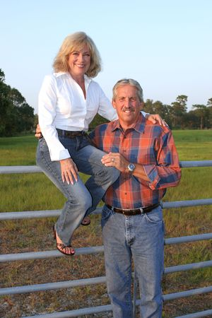 A good looking mature couple on a farm. The wife is sitting on the fence with her husband standing beside her. photo