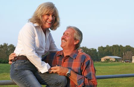 affect: A good looking mature couple on the farm, laughing together.