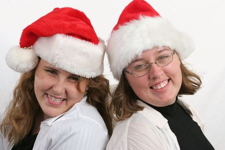 Two attractive sisters in Santa hats.